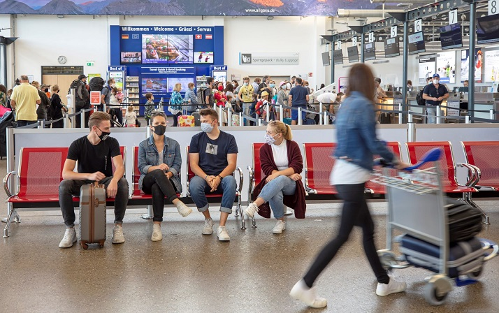 Passengers with corona mask waiting infront of check in counter at Memmingen Airportnt of